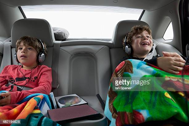 brothers in back seat of car, wearing headphones - family inside car stock photos and pictures