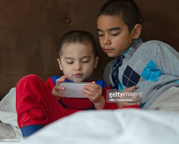 brothers in bed sharing smart phone