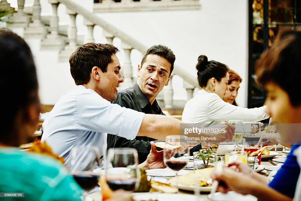 Brothers in discussion during family dinner party : Stock Photo