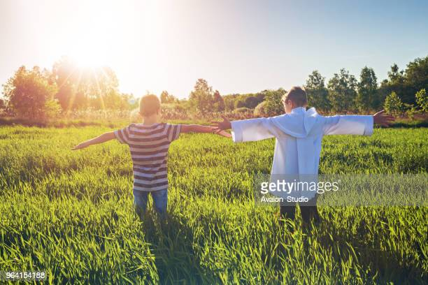 brothers in the meadow look towards the sun - religious celebration stock pictures, royalty-free photos & images