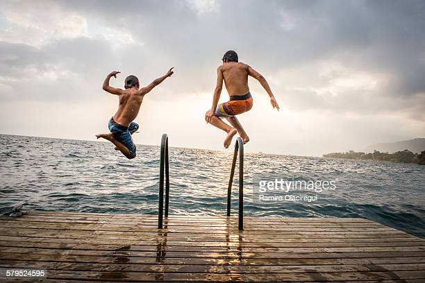 brothers jumping in a lake - standing water stock pictures, royalty-free photos & images