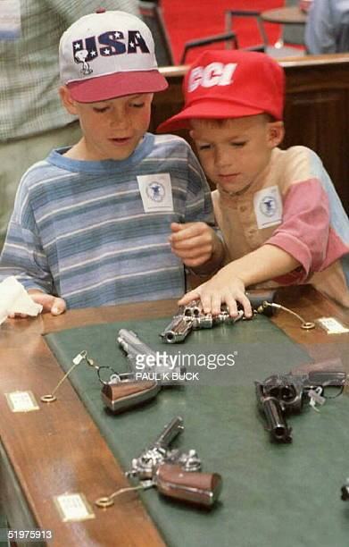 Brothers Kyle and Craig Mayfield sample one of the many firearms on display at the National Rifle Association's 125th Anniversary Annual Meetings and...