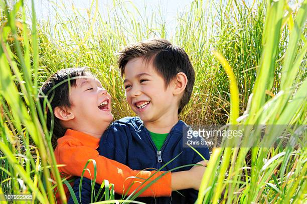 brothers laughing in the grass - newhealth stock pictures, royalty-free photos & images
