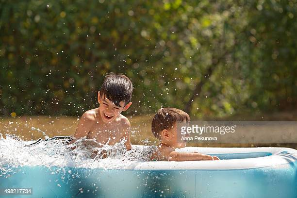 Brothers laughing while playing in inflatable swimming pool