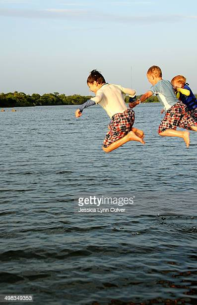 brothers leaping from a dock - lynn pleasant photos et images de collection