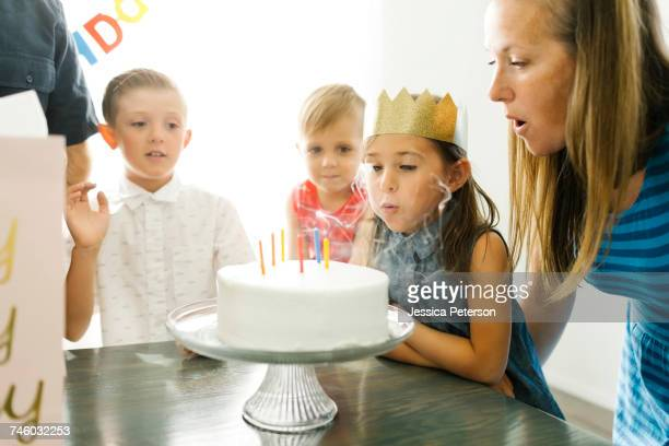 brothers (2-3, 6-7) looking at sister (6-7) and mother blowing birthday candles - happybirthdaycrown stock pictures, royalty-free photos & images