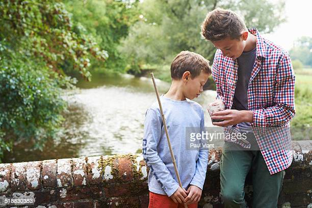 Brothers looking at worms in glass jar