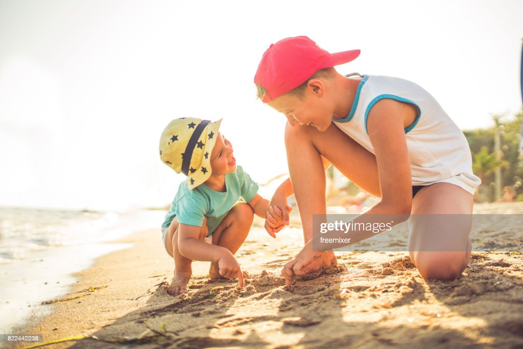 Brother's love and fun time on the beach : Stock Photo