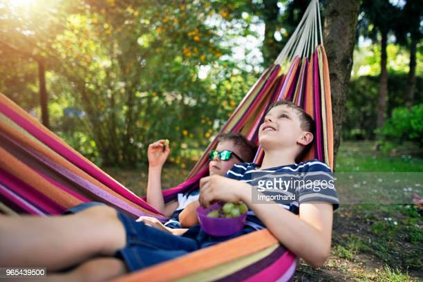 brothers lying on hammock and eating grapes - lazy poland stock photos and pictures