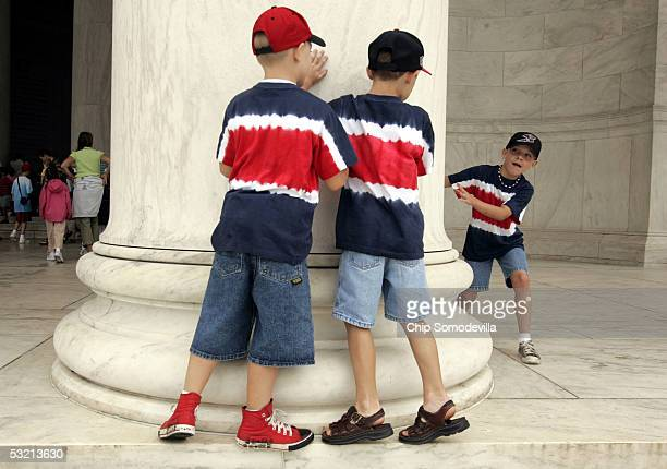 Brothers Nick Rauber Jeff Rauber and Ty Rauber play hideandgoseek around the columns at the Jefferson Memorial July 8 2005 in Washington DC Triplet...