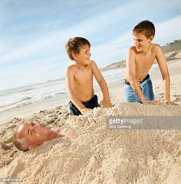 Brothers on a Beach Burying Their Father in Sand