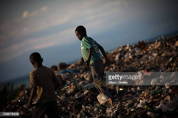 Brothers play at an unofficial dump in front of a community called Village Alpha March 8 2011 in PortauPrince Haiti The dump rising 15 feet above...
