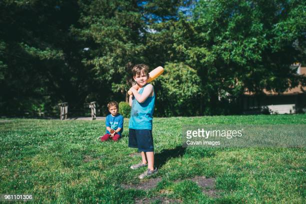 brothers playing baseball at park - batting sports activity stock pictures, royalty-free photos & images