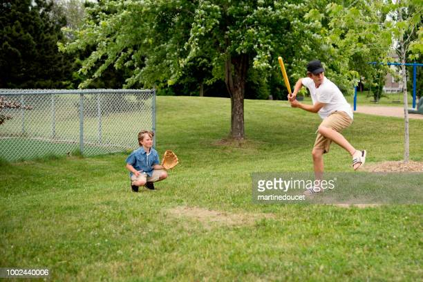 """brothers playing baseball in suburb park. - """"martine doucet"""" or martinedoucet stock pictures, royalty-free photos & images"""