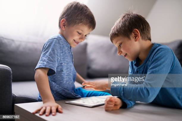 Brothers playing chess using tablet