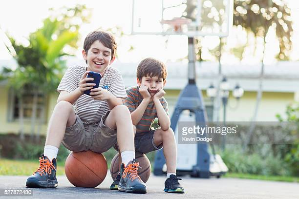 Brothers (6-7), (8-9) playing handheld video game