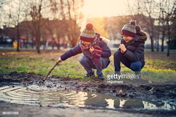brothers playing in a spring puddle - elements stock photos and pictures