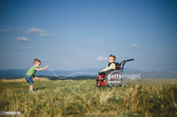 brothers playing in the nature - wheelchair stock pictures, royalty-free photos & images