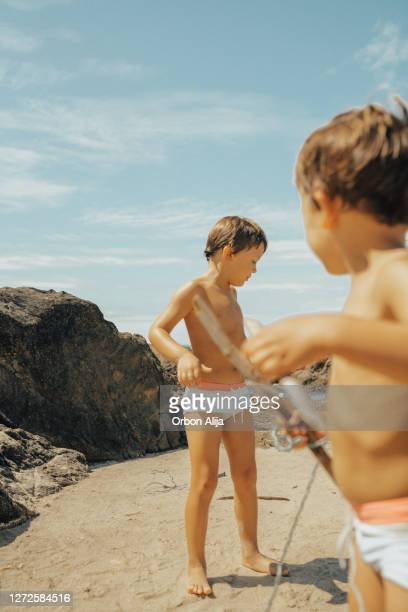 brothers playing in the rocks at the beach - swimwear stock pictures, royalty-free photos & images