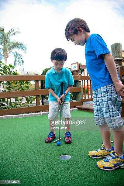 brothers playing miniature golf - putting stock pictures, royalty-free photos & images