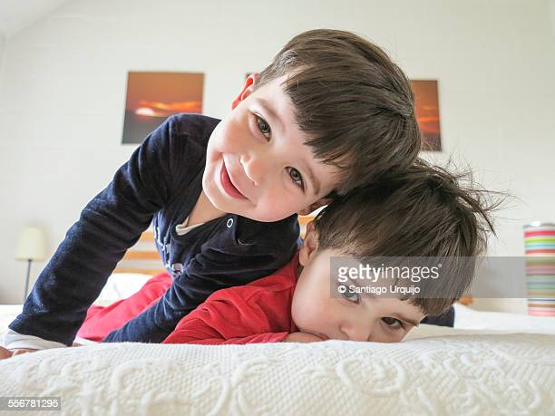Brothers playing on a bed on top of each other
