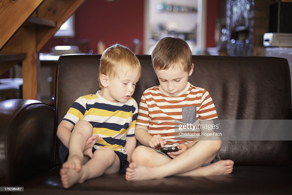 Brothers playing on a smartphone : Stock Photo