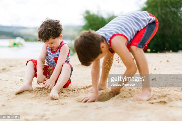 Brothers (4-5, 6-7) playing on beach by lake