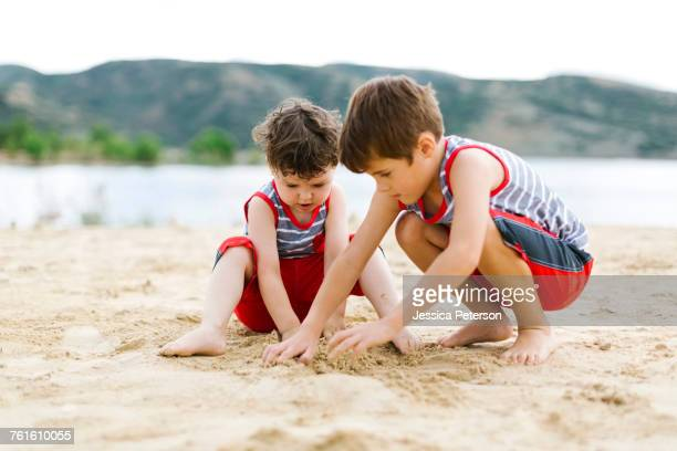 brothers (4-5, 6-7) playing on beach by lake - sandy utah stock pictures, royalty-free photos & images