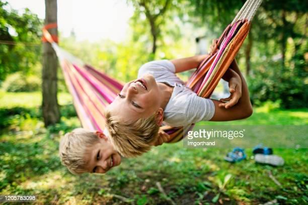 brüder spielen auf hängematte bei sonnenuntergang - nur kinder stock-fotos und bilder