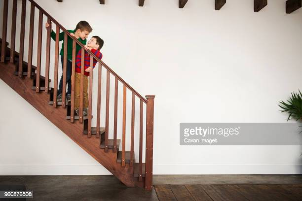 Brothers playing on wooden staircase at home