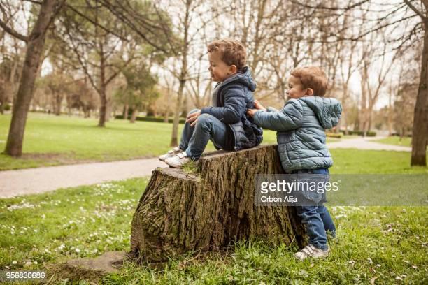 brothers playing outdoors - coat imagens e fotografias de stock