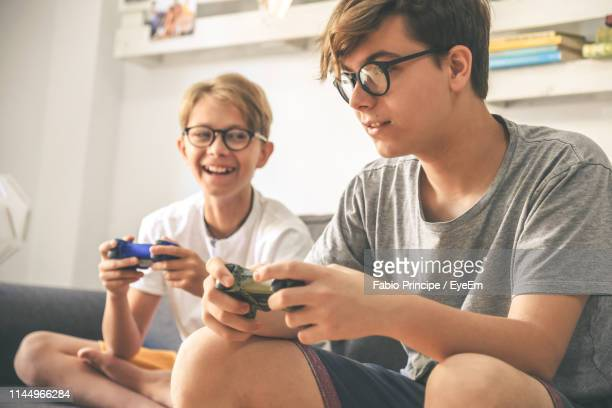 brothers playing video game at home - brother stock pictures, royalty-free photos & images