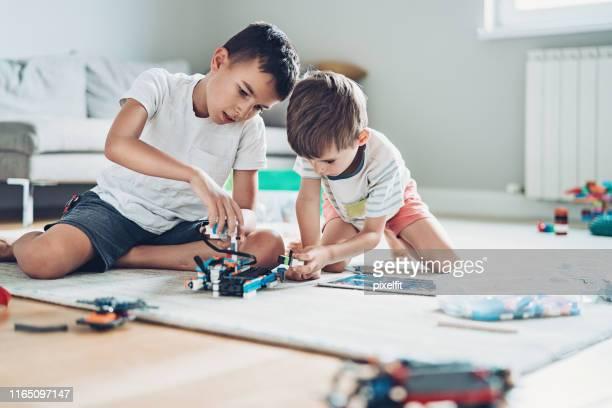 broers spelen met een robot op de vloer - 10 11 jaar stockfoto's en -beelden