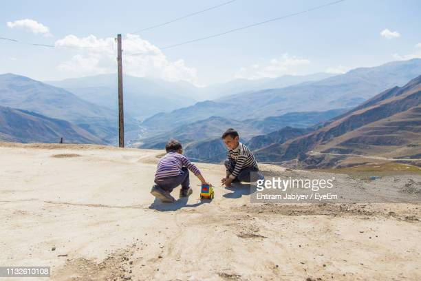 brothers playing with toy car on mountain against sky - azerbaijan stock pictures, royalty-free photos & images