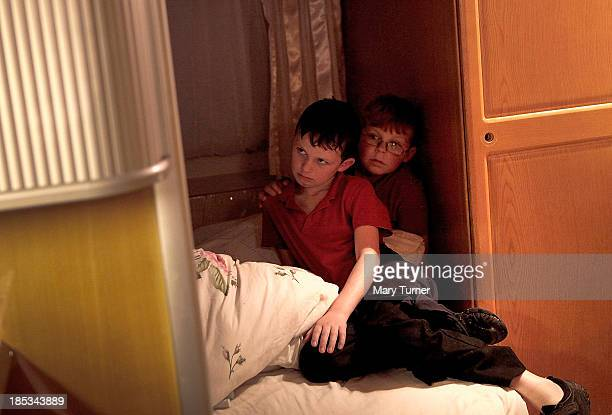Brothers Richard and John Sheridan watch television in their family home on the road outside the Dale Farm site on October 18, 2013 in Crays Hill,...
