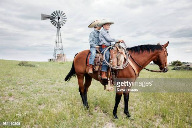 brothers riding horse on grassy field against windmill - ranch stock pictures, royalty-free photos & images