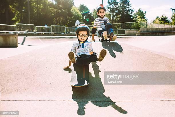 brothers riding skateboards at park - skateboardpark stockfoto's en -beelden