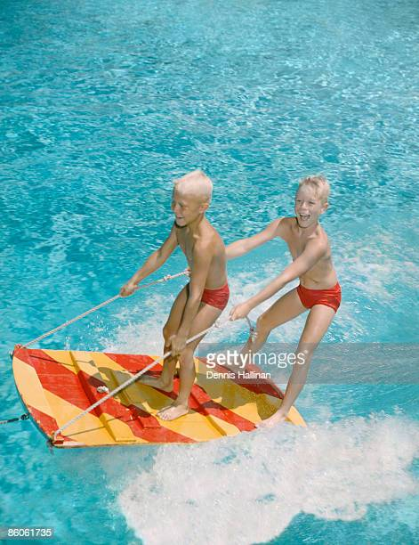 Brothers riding water sled