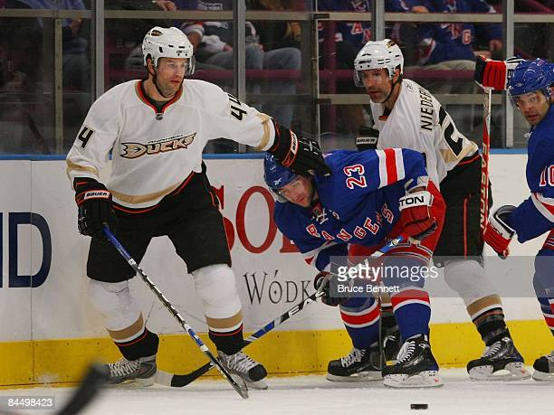 Brothers Rob Niedermayer and Scott Niedermayer of the Anaheim Ducks combine  to check Chris Drury of d66775821