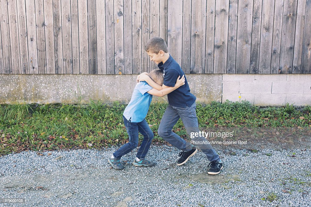 Brothers rough housing outdoors : Stock Photo