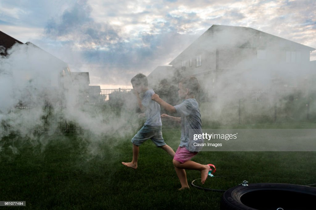 Brothers running amidst smoke at park during sunset : Stock Photo