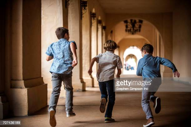 Brothers running near pillars