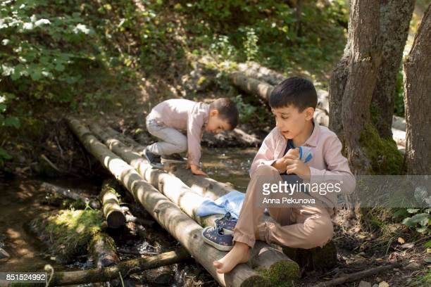 brothers sitting on a wooden posts serving as bridge - stockings no shoes stock pictures, royalty-free photos & images