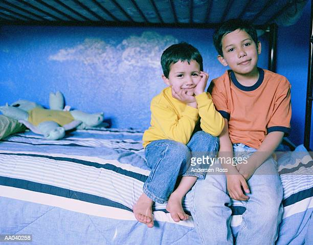 Brothers (3-6) sitting on bottom half of bunk bed, portrait