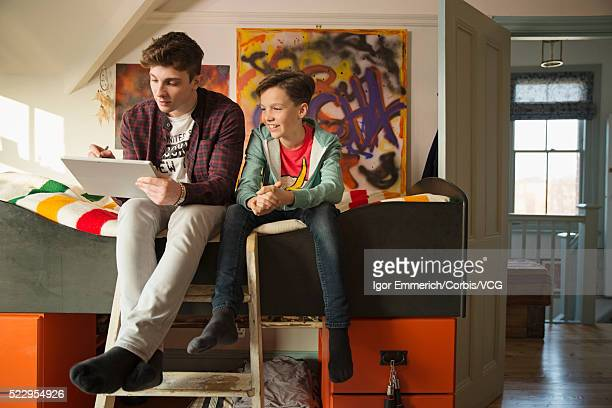 Brothers sitting on bunkbed with digital tablet, abstract paintings on wall, door open