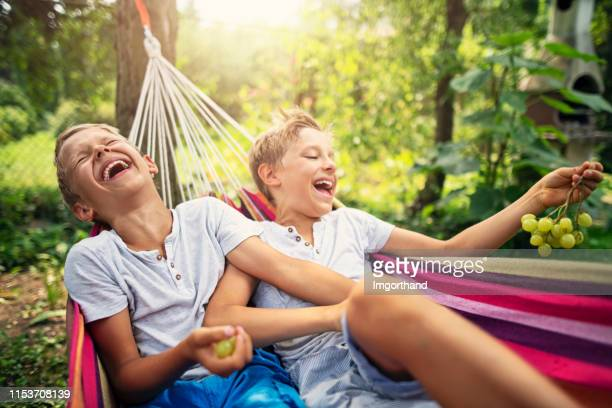 brothers sitting on hammock and eating grapes - brother stock pictures, royalty-free photos & images