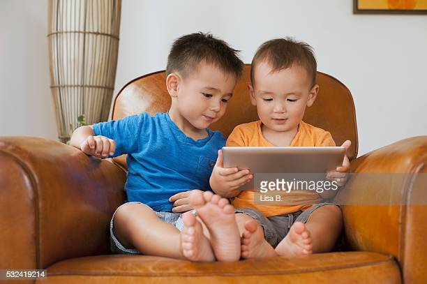 brothers (6-11 months, 12-23 months) sitting on sofa with tablet pc - 6 11 months stock pictures, royalty-free photos & images