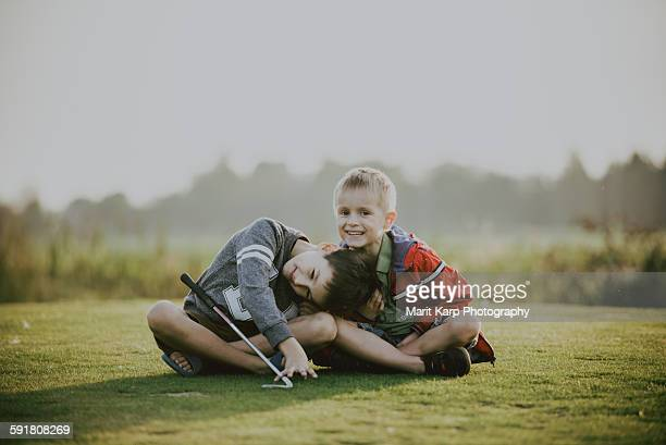 Brothers sitting on the golf field and laughing