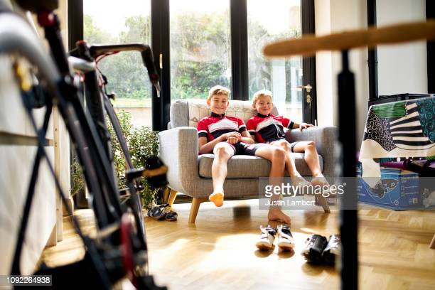 brothers sitting smiling on a couch together before a bike ride - saltdean stock pictures, royalty-free photos & images