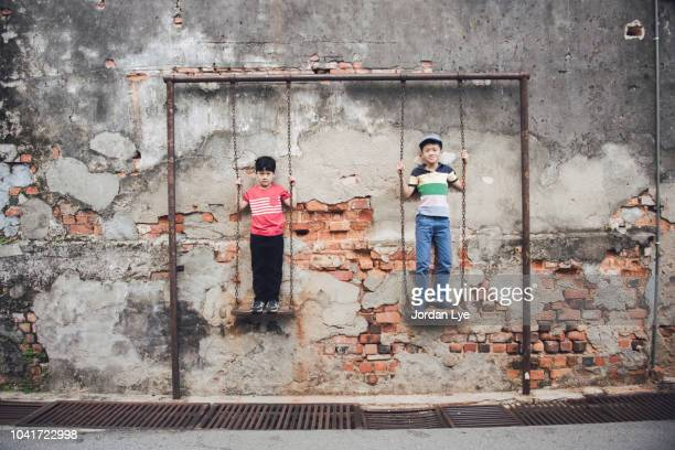 brothers stand on swing - george town penang stock photos and pictures